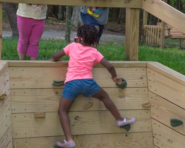 Maxine is climbing a wall.