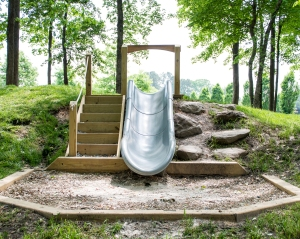 There is a slide playset. on one side there are rocks in a steps pattern and on the other side there are wooden steps with a rope handle