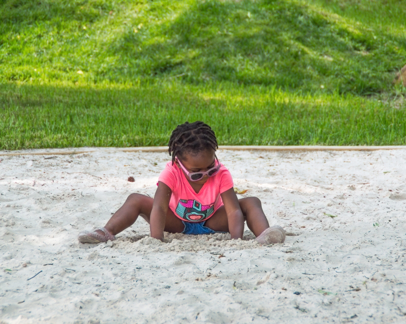 Maxine is playing in a large sandbox