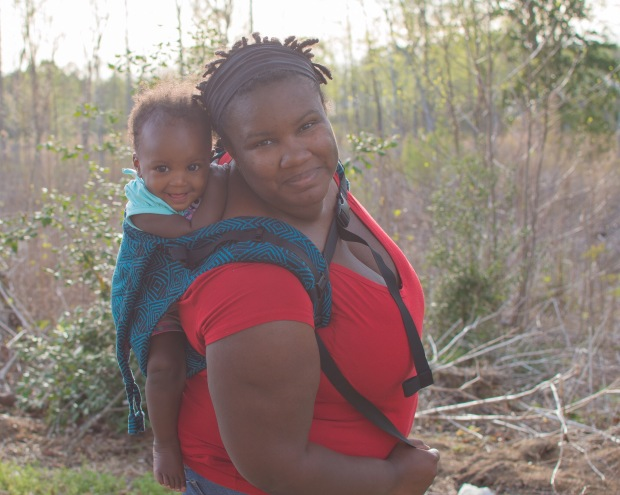 Brittany and Minerva are standing outside. Minerva is on Brittany's back in a blue and black geometric print onbuhimo. Brittany smiles into the camera while Minerva looks just off camera with a huge smile on her face. They are leaning toward the camera.