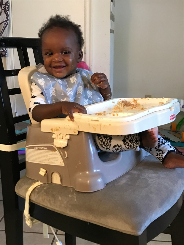 Minerva sits in her high chair. She's smiling and is covered in peanut butter and pasta