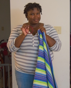 Brittany holding a red sling ring in her hand and a blue, green, white, and purple woven wrap in the other hand