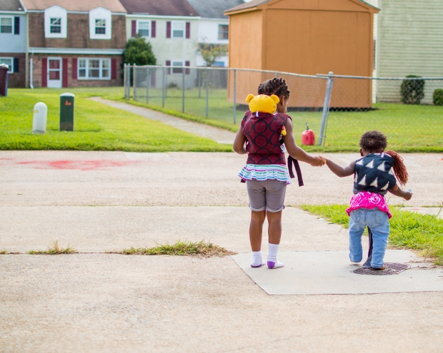 Maxine and Minerva holding hands walking down the driveway. Maxine is wearing a toy in  a red and black carrier and minerva is wearing a black and white ikat print carrier