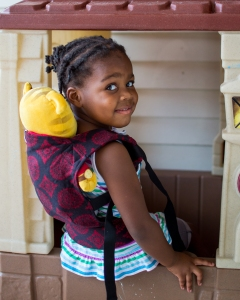 maxine staring at the camera in a black and red carrier that is holding daniel tiger on her back