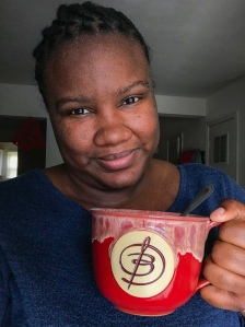 Brittany, holding a deep red latte mug with a B on it, smiles into the camera.